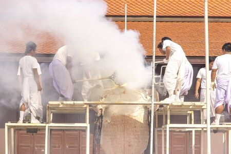 Buddhist in white cloth making buddha image in pouring process smoky background
