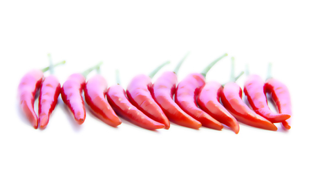 straight line: Blurring red chili pepper straight line on white background