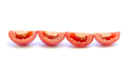 straight line: Tomatoes sliced in straight line on white background