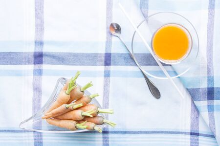 carot: Baby carrots juice glass with raw ingredient on blue table mat Stock Photo