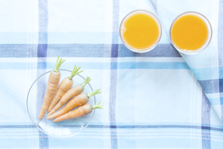 carots: Carot juice and fresh baby carots on table mat Stock Photo