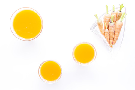 carots: Baby carrots and juice sized arrange on white background Stock Photo