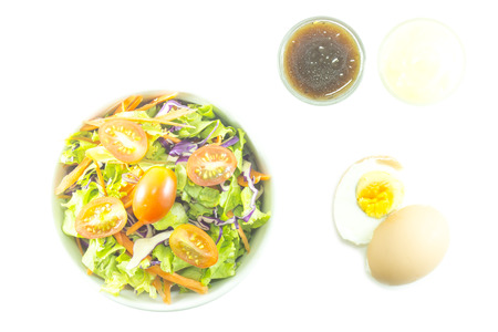 Fresh salad with dressing and boiled egg on white background