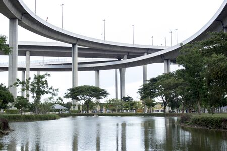 tollway: Water reflection bridge structure with lake green park Stock Photo