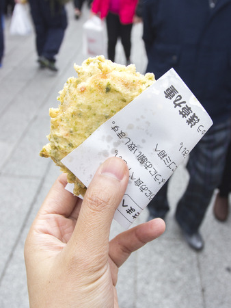 small paper: Mochi crispy fried street food in Japan cover with small paper