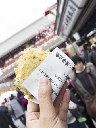 small paper: Mochi crispy fried traditional street food in Japan cover with small paper