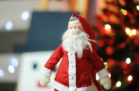 Tilde toy Santa Claus on a background of glowing lights Christmas tree and snowman