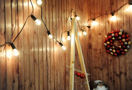 Retro garland of glowing bulbs on a wooden wall. Christmas mood. Wreath of Christmas balls on the background Stock Photo