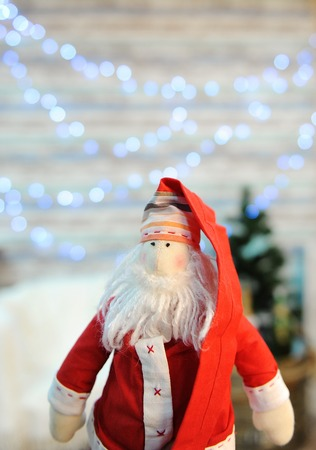 Tilde toy Santa Claus on a background of glowing lights wall and Christmas tree