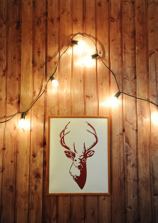 Picture deer on a wooden wall with retro garland of glowing bulbs. Christmas mood