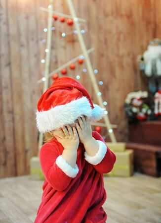 The child in the Santas cap closes eyes palms. Christmas decorations in the background