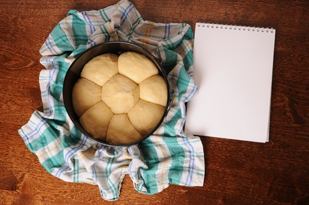 top veiw: Pie before baking is in round dish on a checkered towel on wooden table with blank sheet for text