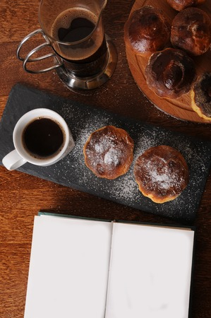 top veiw: Pie before baking is in round dish on a checkered towel on wooden table. Open book with free place for text or design
