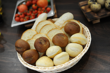 pone: Basket with bread. Wheat and rye bread rolls, toast. Tomatoes in the background