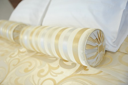 Decorative pillow-cushion of golden fabric on the bed. Element of luxury interior