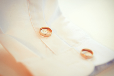 Wedding rings on a buttons of white grooms shirt Stock Photo