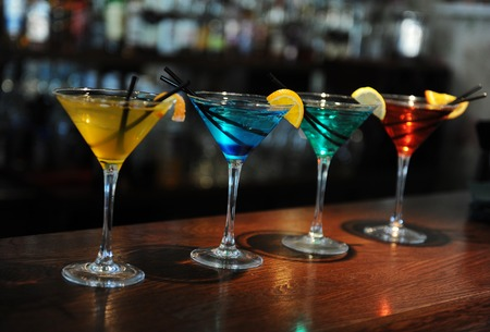 sweet vermouth: Four colored stay cocktails on the bar. Yellow, blue, turquoise, red. Decorated with a lemon slice Stock Photo