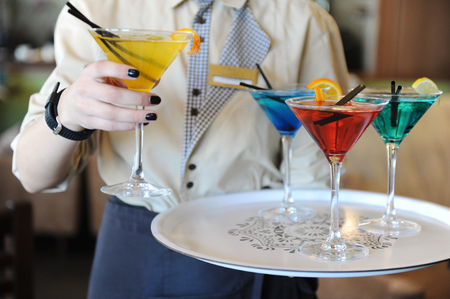 delivers: Waiter delivers four colored cocktails on the tray. Yellow, blue, turquoise, red. Decorated with a lemon slice
