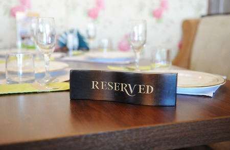 lunch table: The wooden label reserved on the table in the restaurant