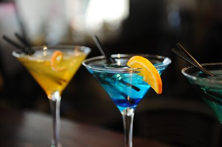 alcohol series: Three cocktails on the bar. Yellow, blue, turquoise. Blue in the center. Decorated with a lemon slice
