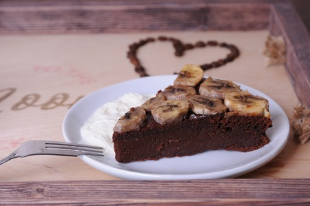 A piece of chocolate cake with banana on a white plate. Close-up. Heart of coffee beans at the background on wooden tray Stock Photo