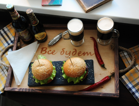 believable: Burgers on a wooden tray. Beer and glasses on served table. The atmosphere is fun. For two