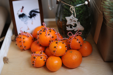Tangerines, decorated with cloves and red-white lace. Close-up on a background of fur-tree branches in a glass vase with a wood star and deer. Rooster picture framed