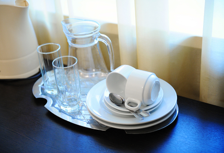 An electric kettle and a tray with a decanter, glasses, cups, saucers, spoons on a table in a hotel room