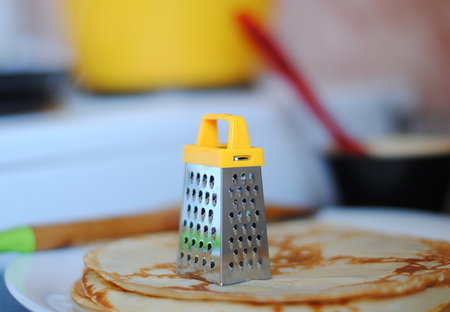 ittle: Miniature yellow grater on a stack of pancakes Stock Photo