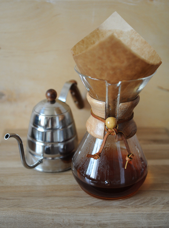 papel filtro: Coffee brewed in the filter paper. Drip Coffee Maker. Wooden background