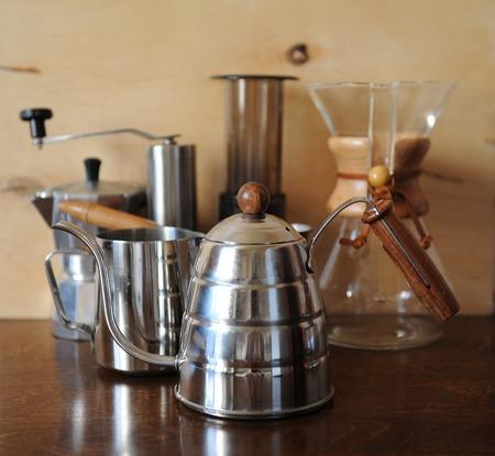 papel filtro: Objetos para la elaboración de café alternativo sobre un fondo de madera. El café de especialidad. Por goteo Cafetera en primer plano Foto de archivo