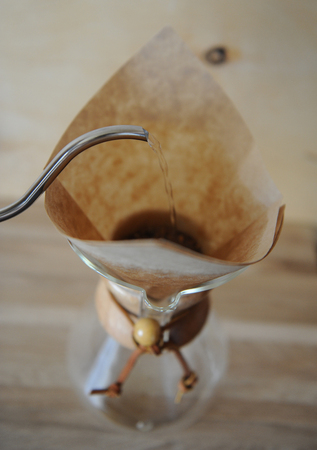 papel filtro: Café preparado en el papel de filtro. Cafetera goteo. De cerca. fondo de madera