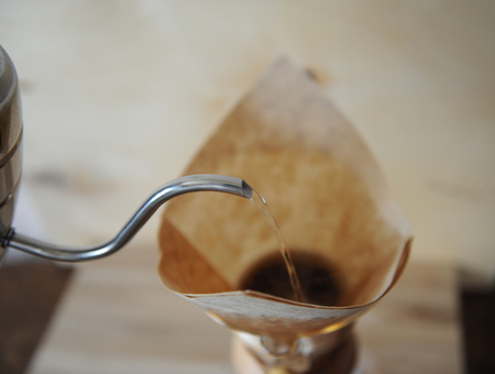 papel filtro: Coffee brewed in the filter paper. Drip Coffee Maker. Close-up. Wooden background