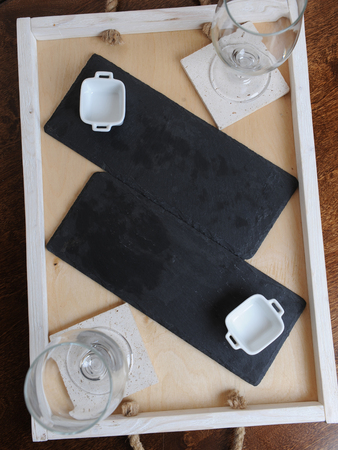 booked: Slate boards, white gravy boat, beer glasses. Free serving on a wooden tray. Space for text Stock Photo
