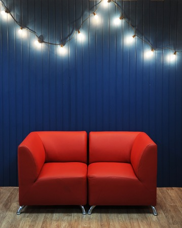 Red leather sofa on a background of blue wall with retro garland of light bulbs. Modern interior. Texture for the design Stock Photo
