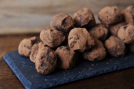 Chocolate truffles in cocoa sprinkled. On the slate board on wooden background. Closeup, texture Stock Photo