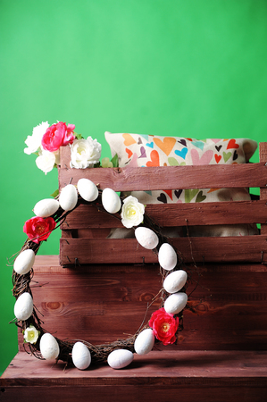 Wooden box with an interior pillow and a bouquet of flowers. Wreath of branches decorated with flowers and eggsGreen background Stock Photo