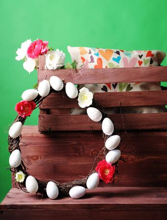 Wooden box with an interior pillow and a bouquet of flowers. Wreath of branches decorated with flowers and eggs. Green background Stock Photo