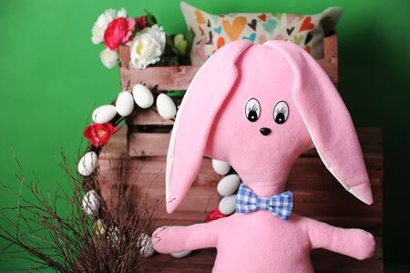 Large pink soft bunny in plaid bow tie with Easter decor. Wooden box with an interior pillow and a bouquet of flowers. Wreath of branches decorated with flowers and eggsGreen background Stock Photo