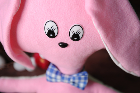 Big cute pink toy soft rabbit in blue plaid bow tie, close-up. Easter decor in the background