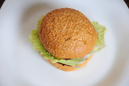 Burger with greens on a white plate top view