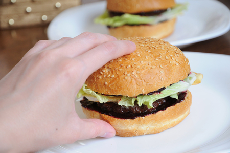 Burger with greens in hand on white plate close up