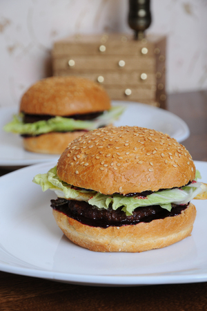 Two burgers with berry sauce on white plates, close up Stock Photo