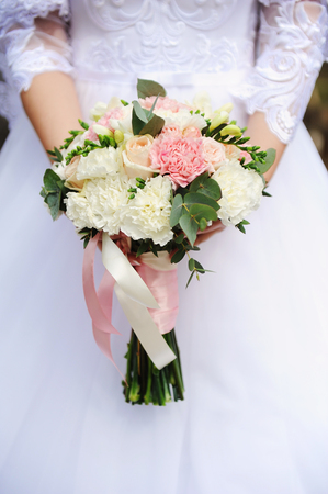 tender tenderness: Wedding bouquet in hands of the bride on background of white dress close-up Stock Photo