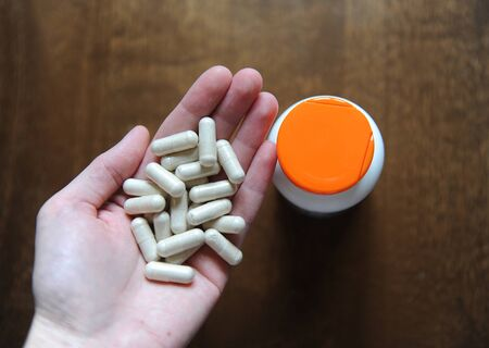 Handful of pills capsules in hand close-up