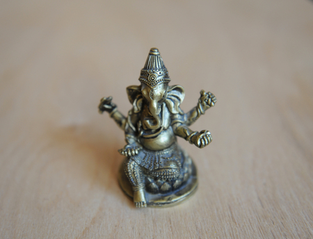 Ganesha figura dorada sobre un fondo claro Foto de archivo