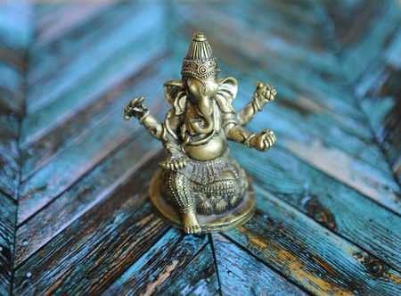esoterismo: Gilded elephant figure of Ganesha on a bright colored parquet background