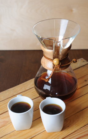 Alternate coffee brewing with filter. Rustic background, white cups Stock Photo