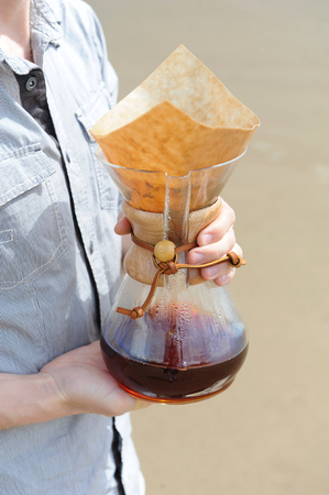 Alternative coffee brewing in hand in the hands of a young man against the background of sandy beach