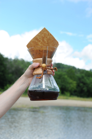 Alternative coffee brewing in hand on background of the river and forest